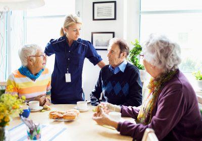 Bild på en samling personer runt om ett bord och fikar